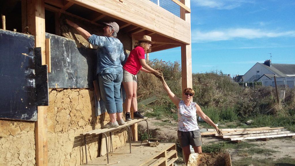 équipe travaillant sur mur terre paille